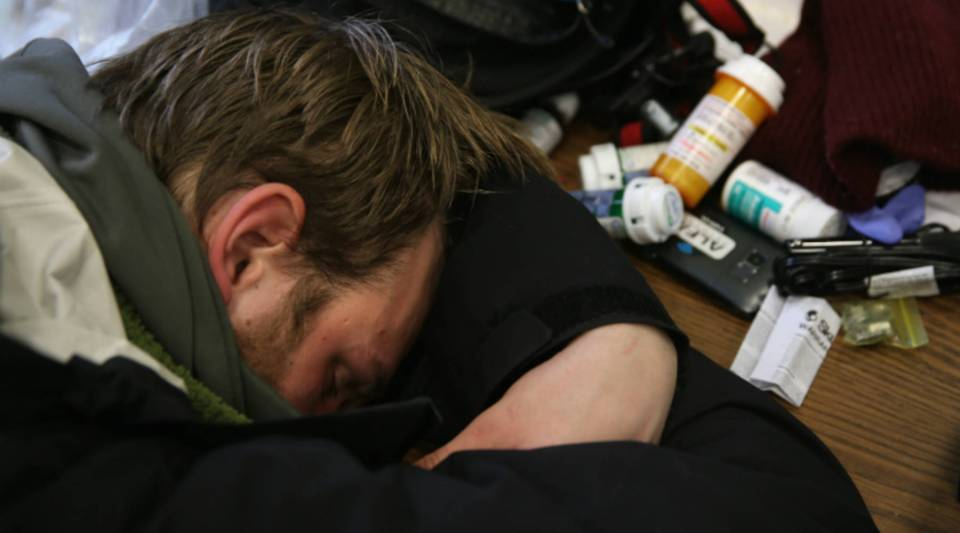 Jackson, 27, who said he is addicted to prescription medication, lies passed out in a public library in New London, Connecticut.