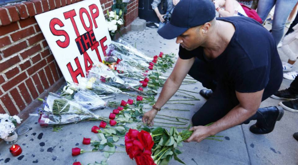 A man lays down roses to honor each victim of the shooting at a gay nightclub in Orlando as people gather outside of the Stonewall Inn in New York City.