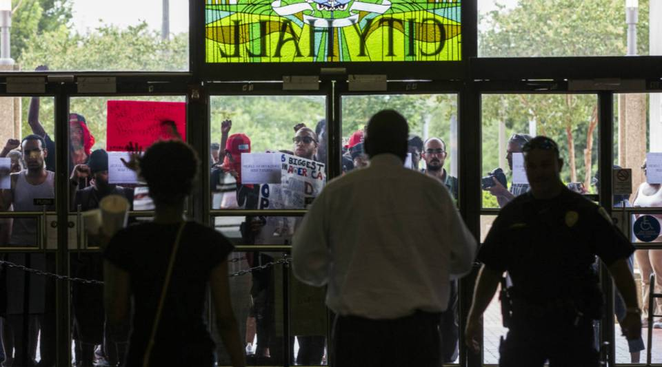Officials keep an eye on a small group of protesters staging a silent protest at the Baton Rouge City Hall on Monday over the Alton Sterling shooting.