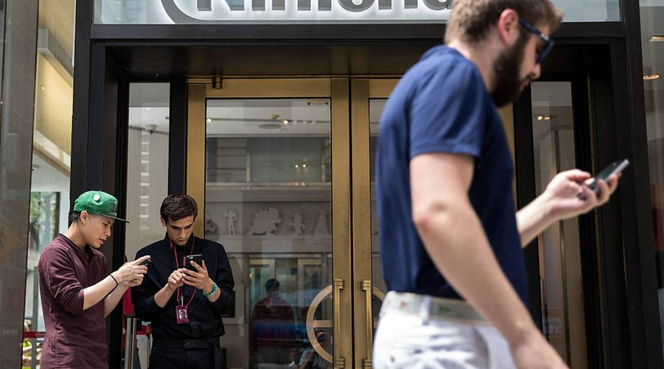 Two men (L) play Pokemon Go on their smartphones outside of Nintendo's flagship store, July 11, 2016 in New York City. The success of Nintendo's new smartphone game, Pokemon Go, has sent shares of Nintendo soaring.
