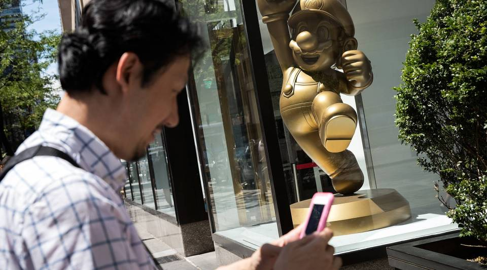 A man plays Pokemon Go on his smartphone outside of Nintendo's flagship store, on Monday in New York City. Businesses are finding creative ways to use the game to attract customers.
