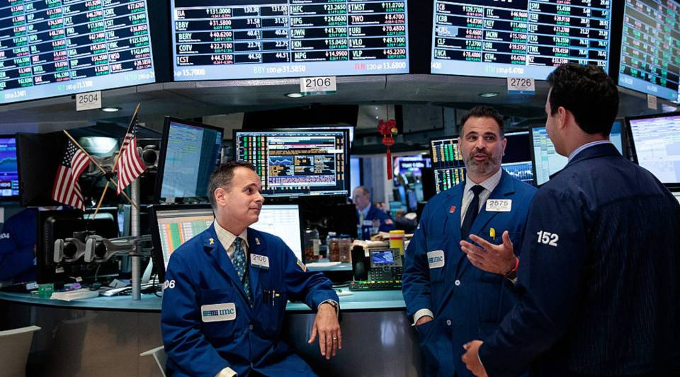 A group of traders talk while working on the floor of the New York Stock Exchange (NYSE), July 12, 2016 in New York City. The Dow Jones industrial average closed at an all-time high.