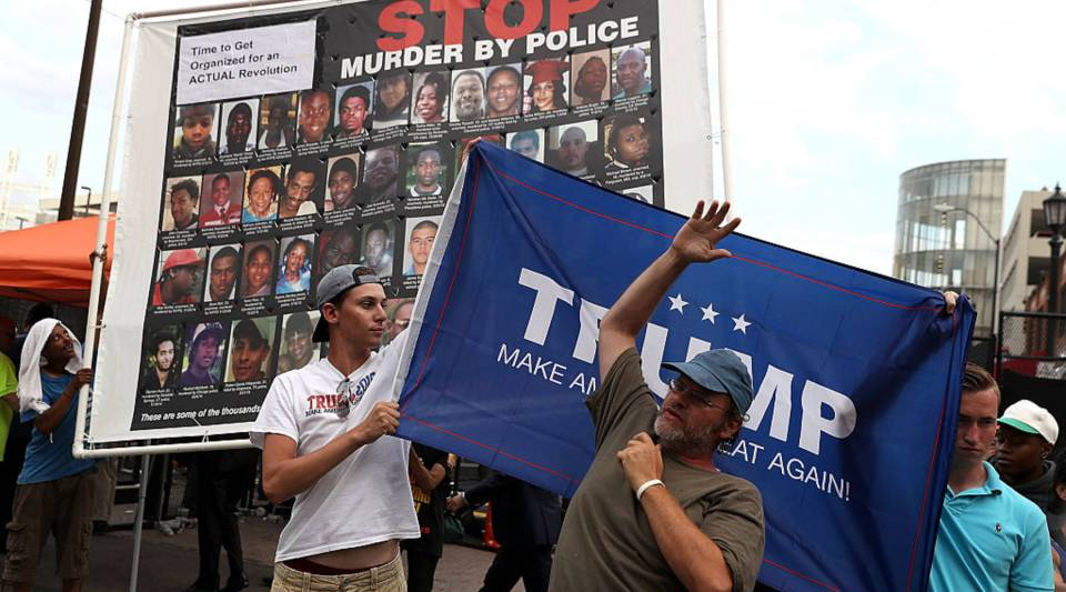 A man tries to block a banner held by supporters of Republican presidential nominee Donald Trump outside the Republican National Convention in Cleveland.