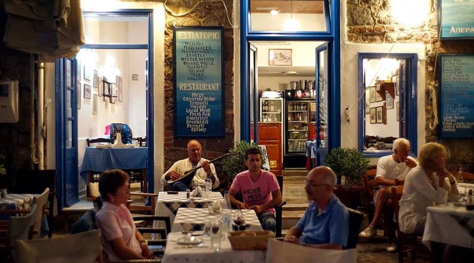 People sitting outside of a restaurant in Greece.