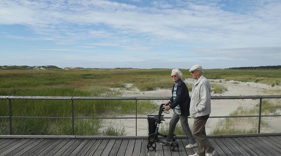 An elderly couple walk along a wooden walkway on vacation in Germany.