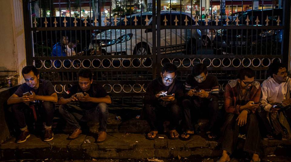 "People play ""Pokemon Go,"" a came partially developed by Alphabet, on smartphones on July 24, 2016 in Yogyakarta, Indonesia."