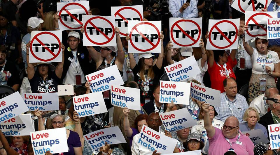 elegates hold up signs that read 'Trans-Pacific Partnership (TPP)' and 'Love trumps hate' during the opening of the first day of the Democratic National Convention at the Wells Fargo Center, July 25, 2016 in Philadelphia, Pennsylvania.
