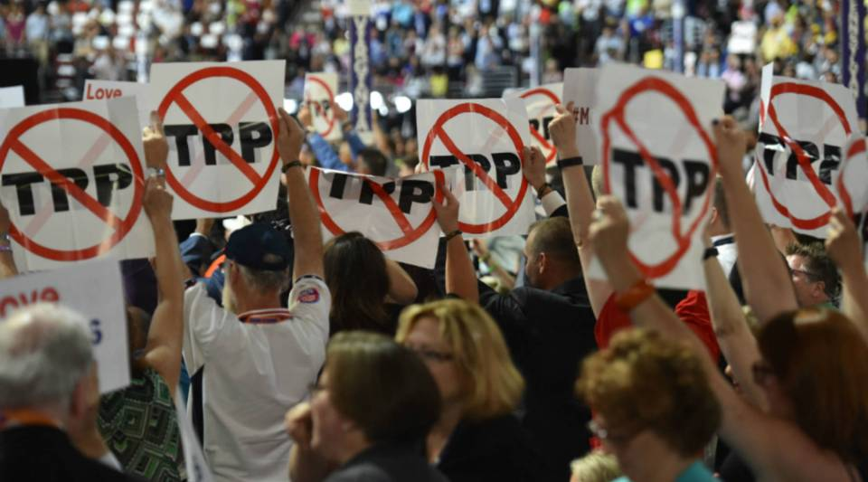 Delegates show their opposition to the Trans-Pacific Partnership during Day 1 of the Democratic National Convention at the Wells Fargo Center in Philadelphia, Pennsylvania.