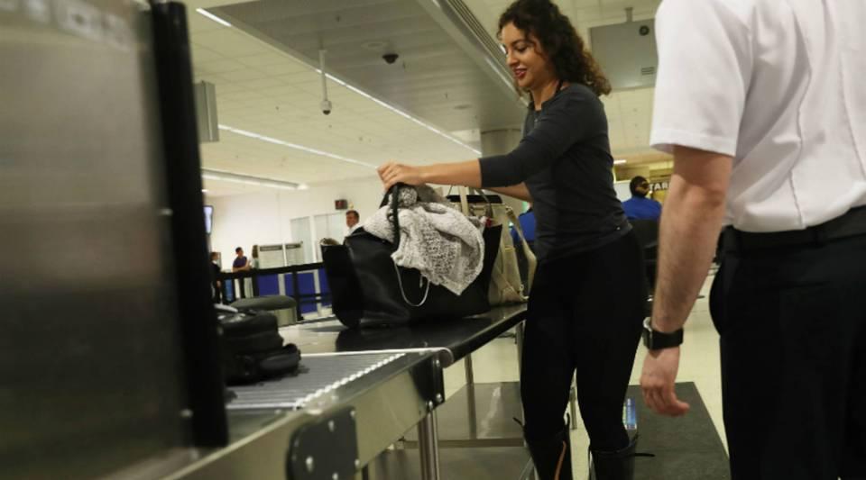 Travelers go through the TSA PreCheck security point at Miami International Airport.