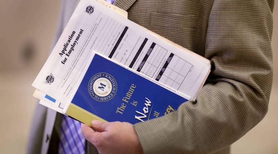 A job searcher holds an employment application as he attends a career fair in West Palm Beach, Florida.