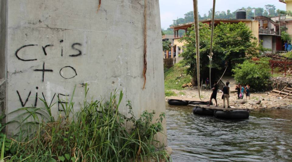 "The words read ""Christ Lives."" Migrants and goods such as oil and foodstuffs are transported illegally on a raft below a bridge that is an official port of entry between Mexico and Guatemala."