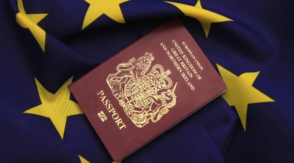 A U.K. passport sits atop the EU flag.