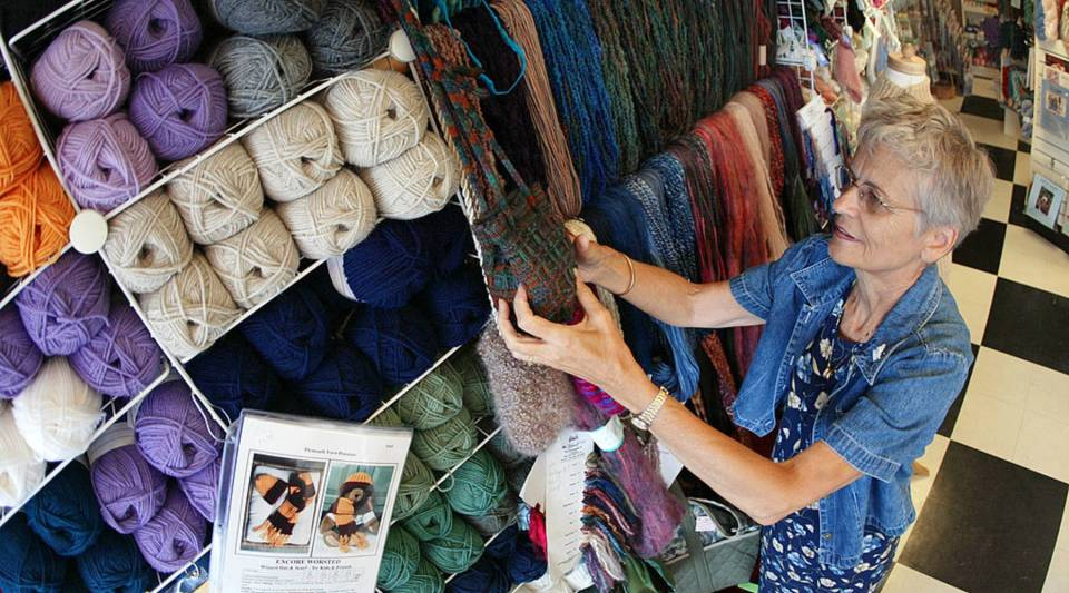 Sixty-eight-year-old Barb Blume arranges yarn at the Mosaic Yarn Studio July 26, 2002 in Des Plaines, Ilinois. Blume is a retired nurse who turned her hobby of knitting into a second career at the yarn studio where she is the assistant manager and knitting class instructor.