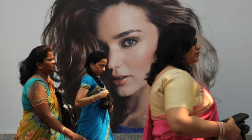 Indian women walk past a billboard of Australian model Miranda Kerr in Mumbai on March 8, 2013.