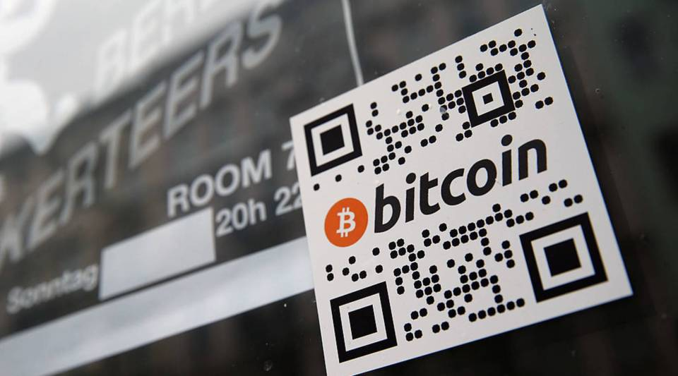 sticker on the window of a local pub indicates the acceptance of Bitcoins for payment.