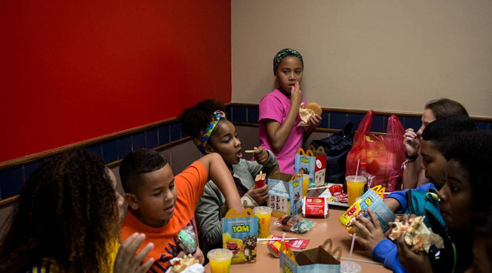 Children from the Cantagalo 'favela' community enjoy happy meals at McDonalds before heading to the Olympic Rugby 7's on August 11, 2016 in Rio de Janeiro, Brazil.