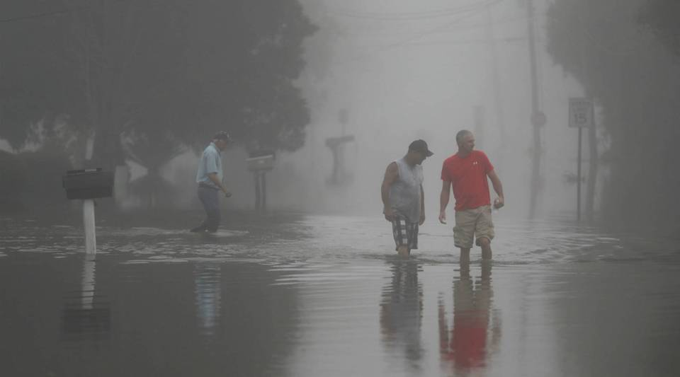 Two people walk through a flooded street in Sorrento, Louisiana as an early morning fog blankets the area.