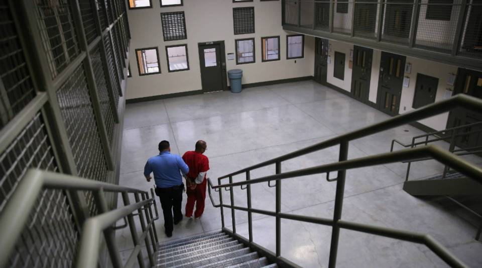 """A guard escorts an immigrant detainee from a """"segregation cell"""" back into the general population at the Adelanto Detention Facility."""