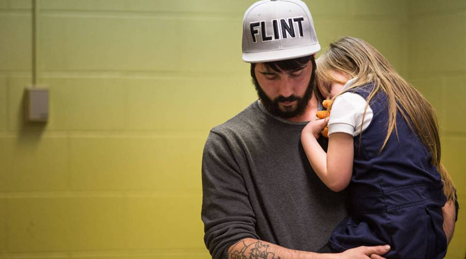 Flint resident Matt Hopper holds Nyla Hopper, 5, after she had her blood drawn to be tested for lead in January. Free lead screenings were performed for Flint children 6 and younger. >