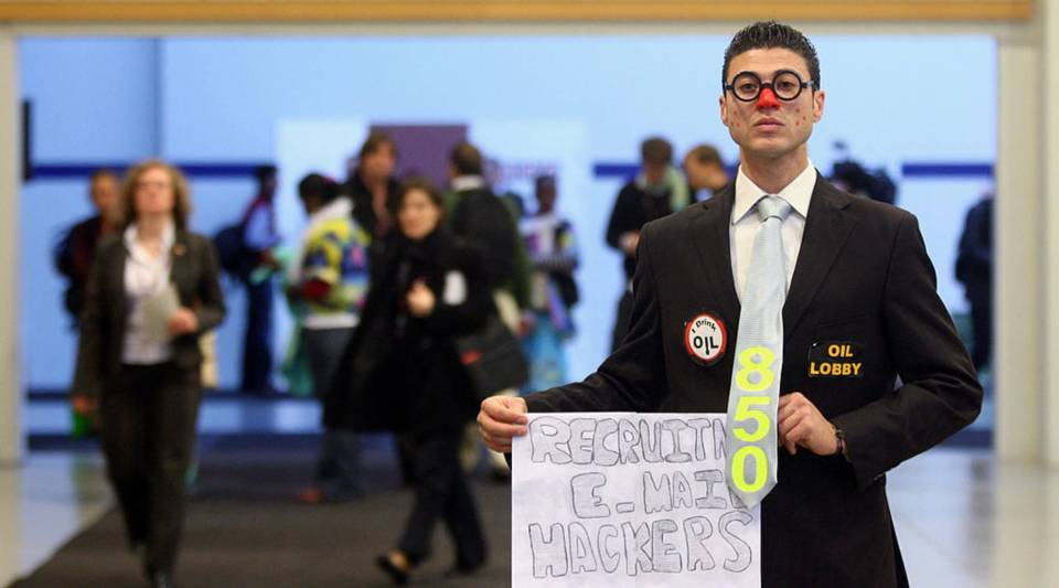An environmentalist dressed as a mock lobbyist holds a banner reading 'Recruting e-mail hackers' during the third day of the United Nations Climate Change Conference in 2009 in Copenhagen, Denmark.