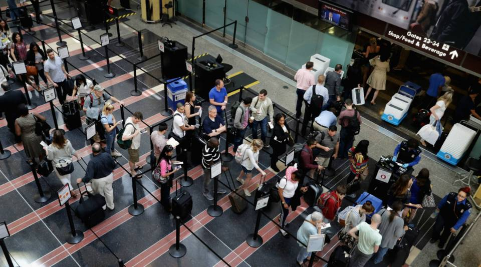 Passengers line up outside a Transportation Security Administration checkpoint at Ronald Reagan National Airport in Arlington, VA.