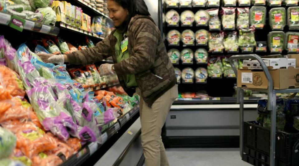 A Wal-Mart employee stocks the produce shelves at a store in Miami, Florida.