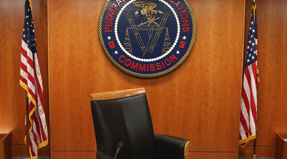 The seal of the Federal Communications Commission hangs behind commissioner Tom Wheeler's chair inside the hearing room at the FCC headquarters in Washington, DC.