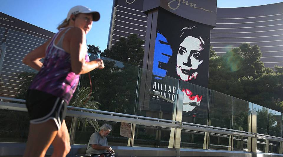 Michael McLean sets up to play his guitar for money near a billboard showing a picture of Democratic Presidential candidate Hillary Clinton advertising the Democratic Presidential debate at the Wynn Las Vegas resort in Las Vegas, Nevada.