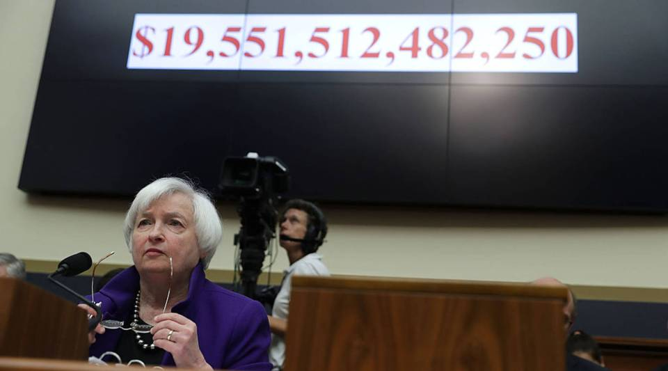 As the number of the current U.S. national debt is seen on a screen, Federal Reserve Board Chair Janet Yellen testifies during a hearing before the House Financial Services Committee on Capitol Hill in Washington, DC.