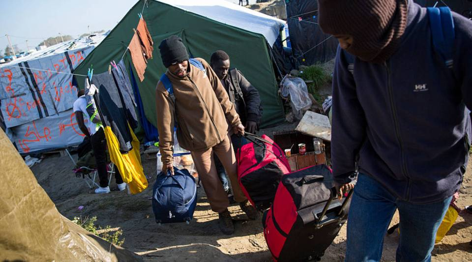 Migrants leave with their luggage at the Jungle migrant camp in Calais, France. Migrants are leaving the Jungle migrant and refugee camp by coach for a second day as French authorities clear the camp of an estimated 7000 people ahead of its demolition.