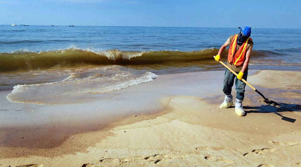 A worker scoops up oil washed ashore from the Deepwater Horizon oil spill in the Gulf of Mexico on June 26, 2010 in Orange Beach, Alabama. Millions of gallons of oil spilled into the Gulf after the April 20 explosion on the drilling platform.