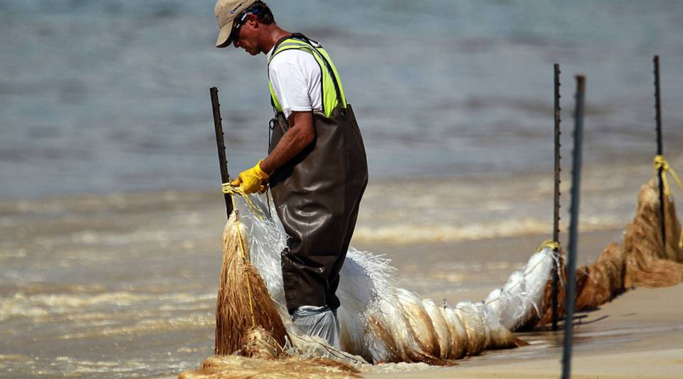 Absorbent material is placed on the beach as oil residue washes ashore from the Deepwater Horizon oil spill in Orange Beach, Alabama, in 2010.