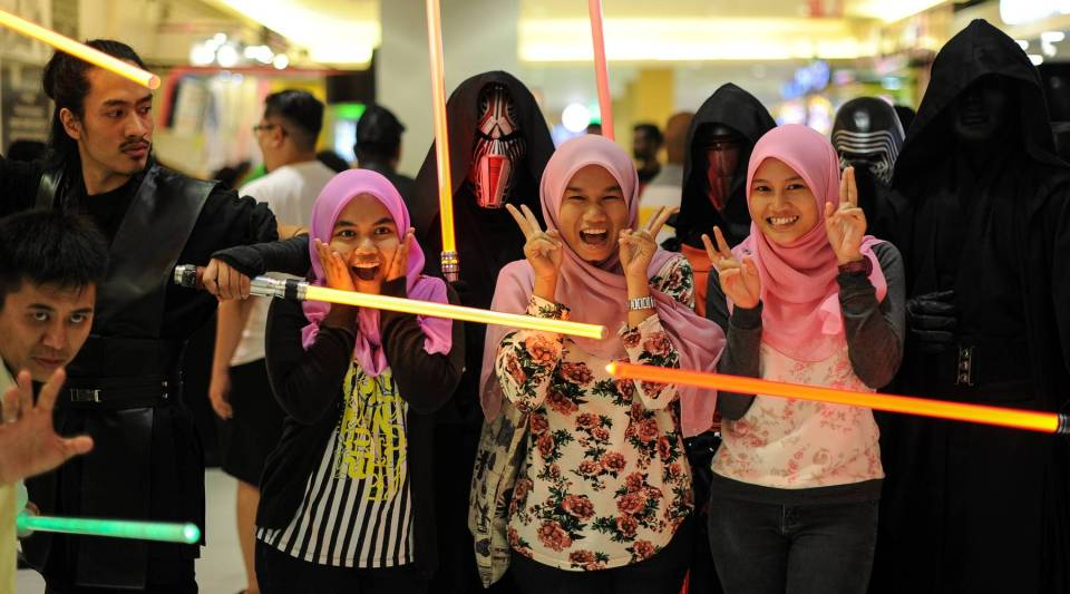 Malaysian Muslim women pose for pictures with members of Malaysia's Star Wars Fan Club dressed as various characters before watching 'Star Wars: The Force Awakens' at a cinema in Subang, outside Kuala Lumpur on December 17, 2015.