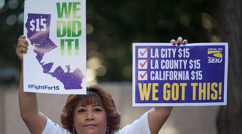 A Service Employees International Union member celebrates after California Governor Jerry Brown signed landmark legislation SB 3 into law on April 4, 2016 in Los Angeles, California.