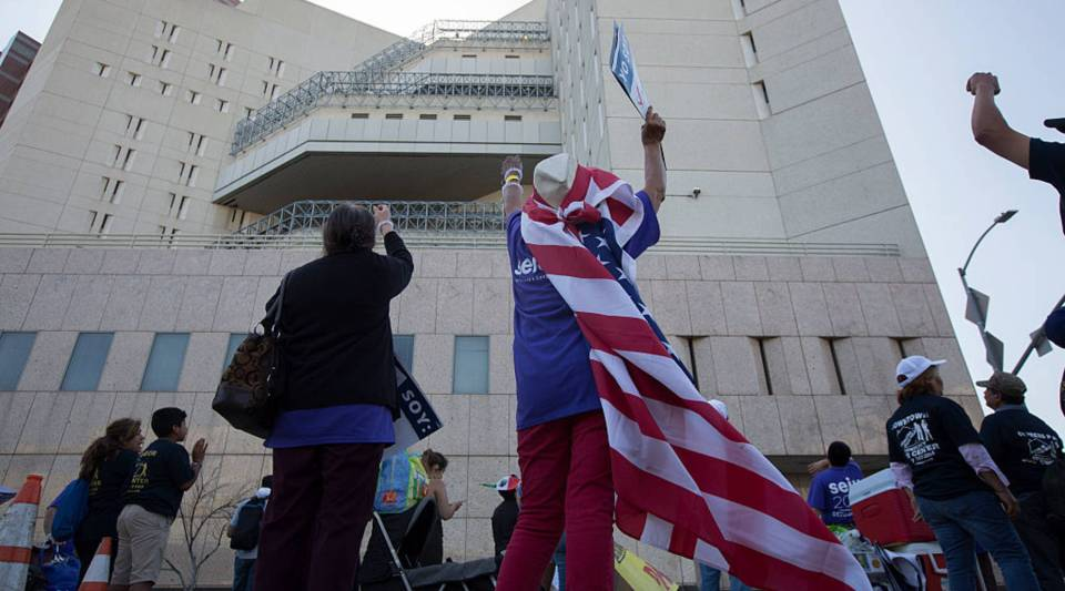 "People wave and call ""We are here"" and ""You are not alone"" in Spanish to immigrant detainees at the Metropolitan Detention Center during one of several May Day marches in Los Angeles earlier this year."