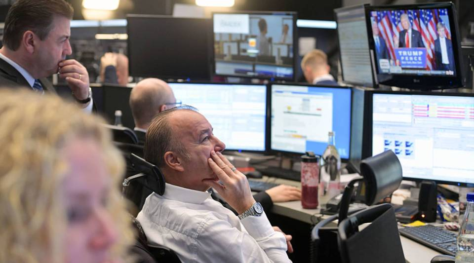 Traders at the Frankfurt Stock Exchange watch Donald Trump after he wins the U.S. presidential elections.