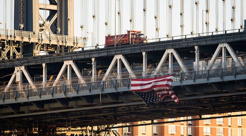 Hung by anti-Donald Trump protestors, an upside down American flag hangs from the side of the Manhattan Bridge on November 14, 2016 in New York City.