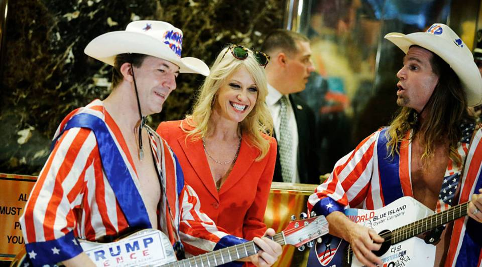 Kellyanne Conway, senior advisor to US President-elect Donald Trump's transition team, jokes with two 'Naked Cowboys' after she exits the elevators during meetings on November 28, 2016 at Trump Tower in New York.