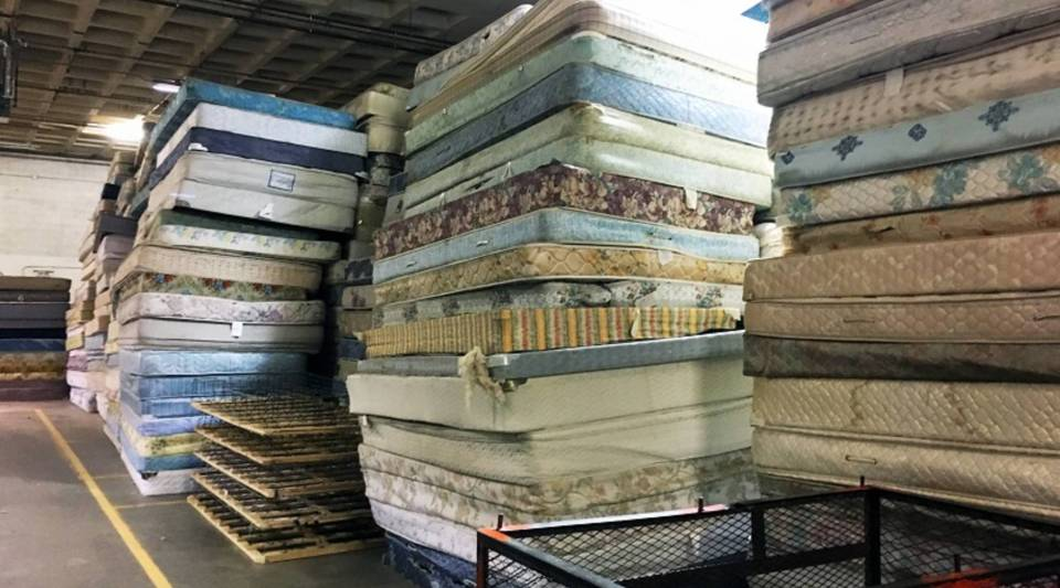 Mattresses piled on the warehouse floor at Goodwill Industries in Duluth, Minnesota. Ultimately, as part of the recycling process, each of these mattresses will be deconstructed and separated into component parts.