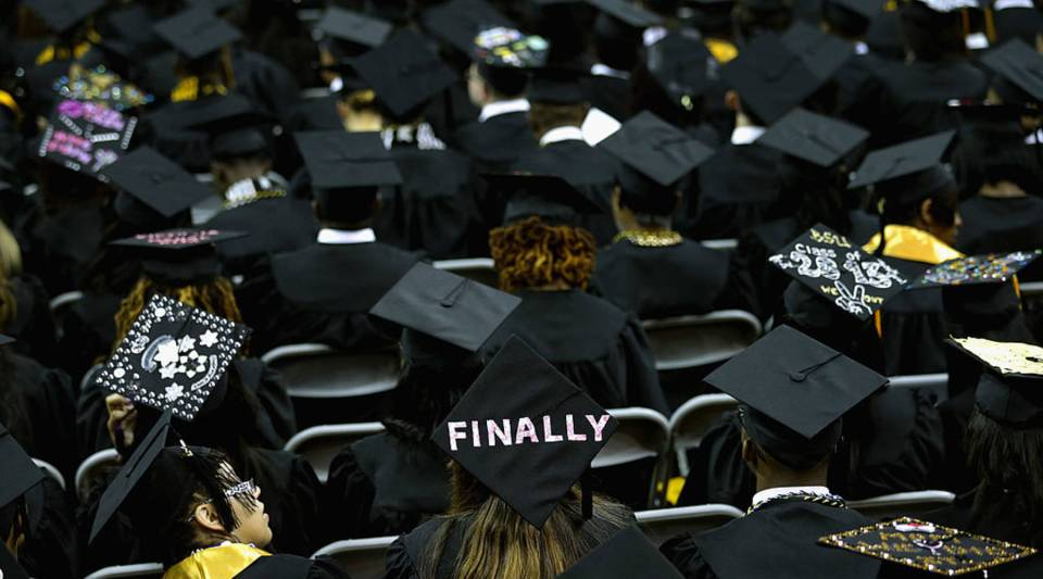 Graduates of Bowie State University put messages on their mortarboard hats during the school's graduation ceremony at the Comcast Center on the campus of the University of Maryland May 17, 2013 in College Park, Maryland.