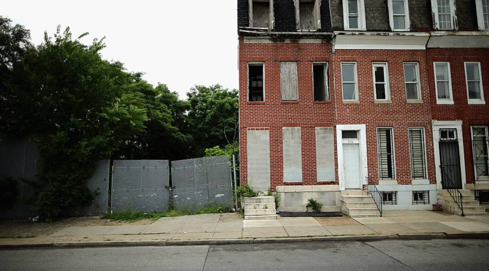 Cinderblocks wall off the door and windows of a burned and abandoned rowhouse across the street from First Mt Calvary Baptist Church, in the Winchester-Sandtown neighborhood June 15, 2015 in Baltimore, Maryland.