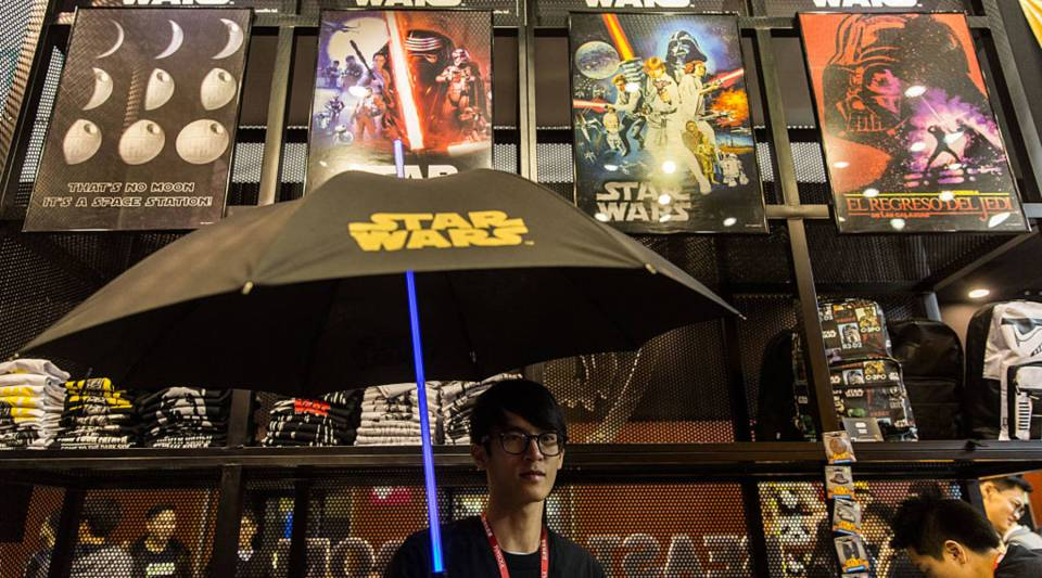 A member of staff demonstrates a Star Wars Jedi 'Lightsaber' themed umbrella at the 'Toy Soul 2015' exhibition in Hong Kong on December 19, 2015. The exhibition which runs from 18-20 December is geared towards local artists and toy developers showcasing new products.