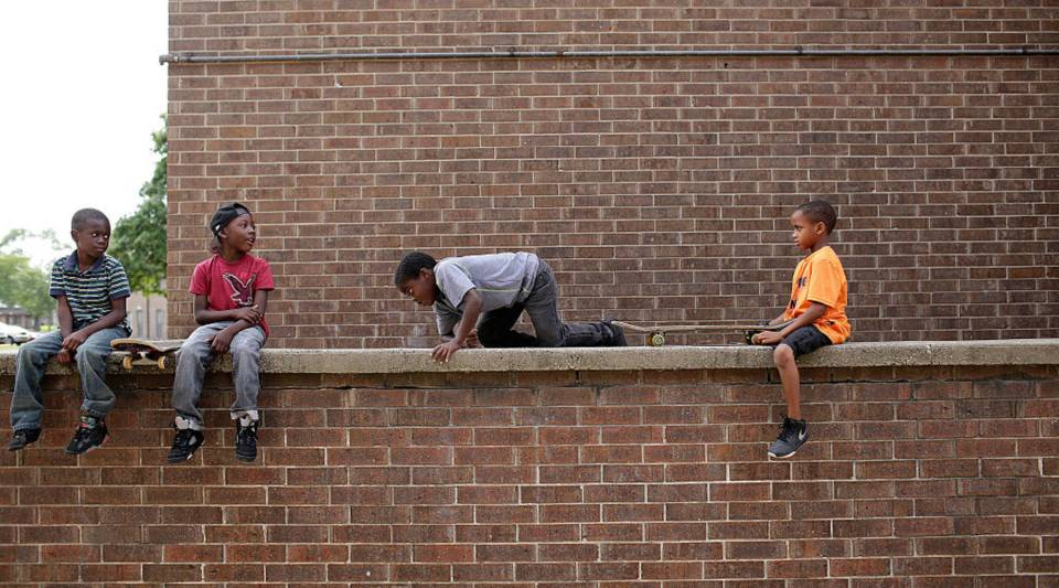 Brysten Edwards, second from left sits with other boys on a wall ledge at the West Calumet Housing Complex on September 4, 2016 in East Chicago, Indiana. The soil at the complex has been found to contain high levels of lead and arsenic putting all residents in danger if exposed to the elements. Edwards was tested for lead poisoning and his results came back positive. Over 1,000 residents are being asked by the East Chicago Housing Authority to relocate, after plans were decided to demolish the housing complex.