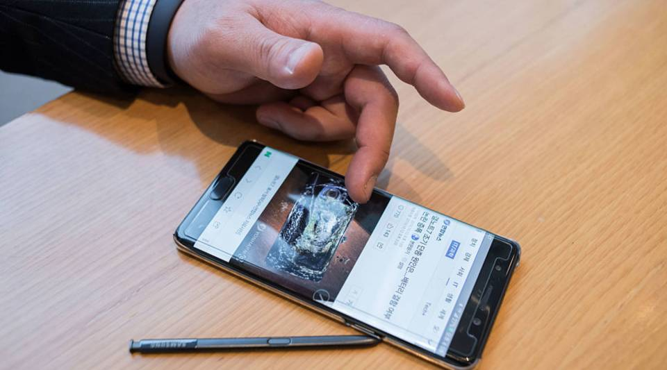 A Samsung customer browses a web page showing a fire-damaged Samsung Note 7 mobile phone, on a similar device, at a Samsung store in a mall beneath the company's headquarters in the Gangnam district of Seoul on October 12, 2016.