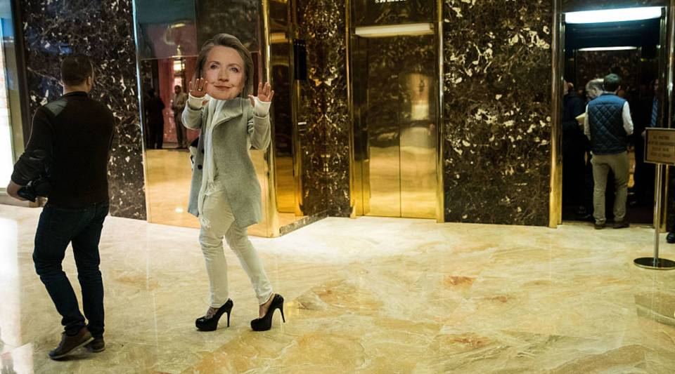 A person wearing a Hillary Clinton mask walks through the lobby at Trump Tower, December 8, 2016 in New York City.