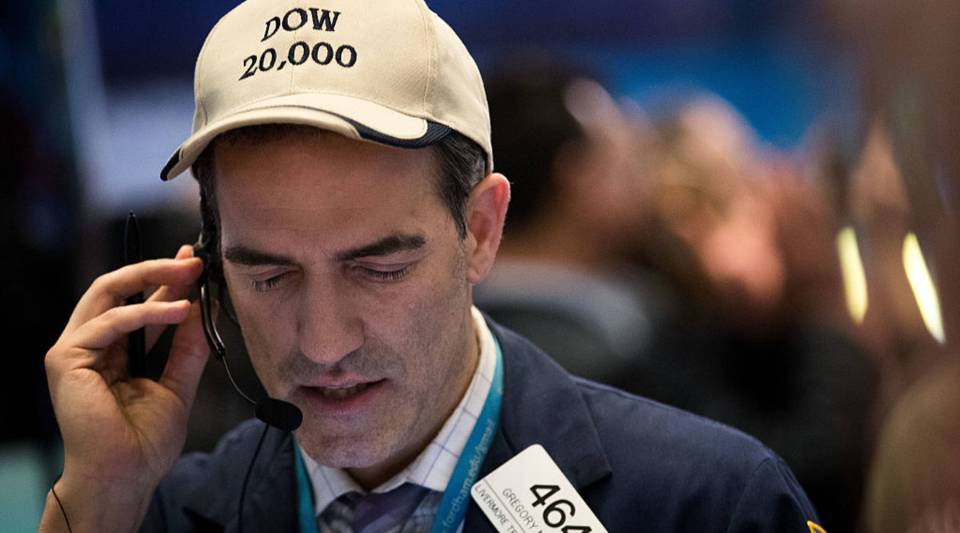A trader wearing a 'Dow 20,000' hat works on the floor of the New York Stock Exchange (NYSE), December 20, 2016 in New York City.