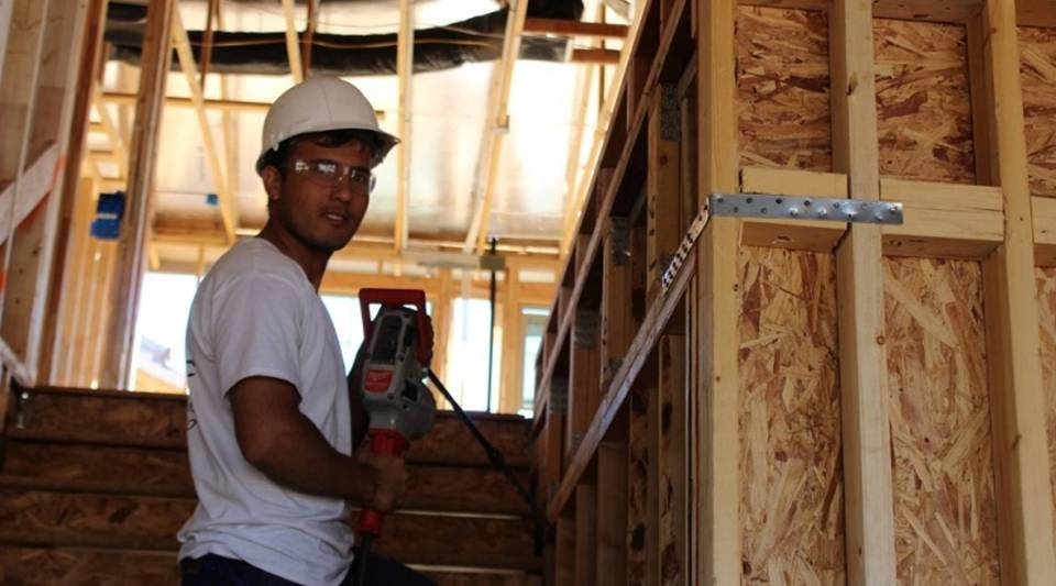 Nasrullah Shinwari works with Austin Electric to add electrical wire to a five-bedroom house before drywall is added.