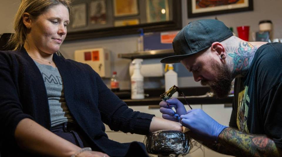 """Kyle Mack tattoos the phrase """"she persisted"""" on to the arm of Lindsay Wenner inside the Brass Knuckle Tattoo Shop in Minneapolis Tuesday, Feb. 21."""
