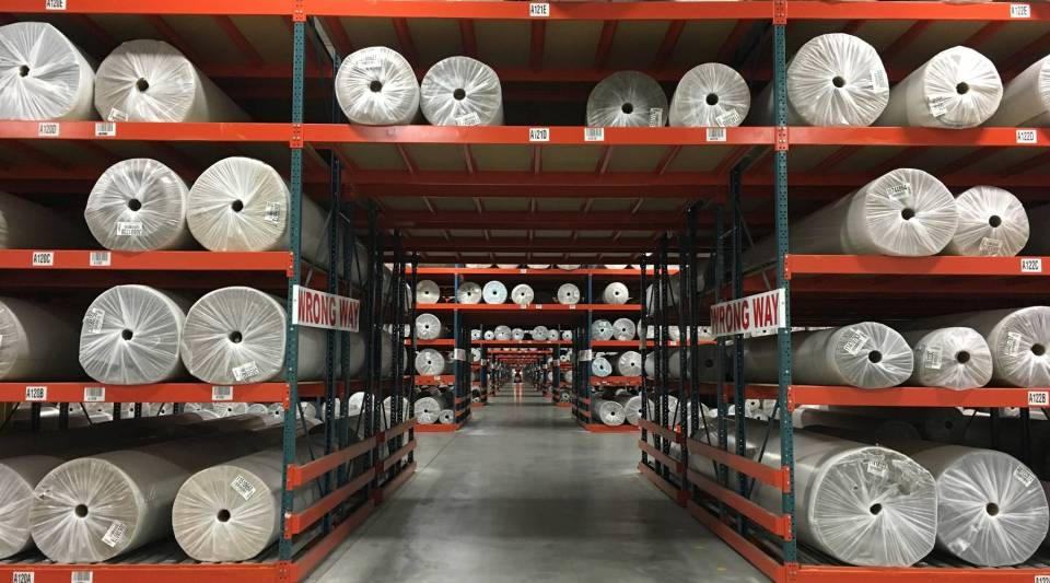 """Workers at Engineered Floors in Dalton, Georgia, call this """"the tunnel,"""" because you can't see from end to end of the stacks of finished rolls of carpet."""