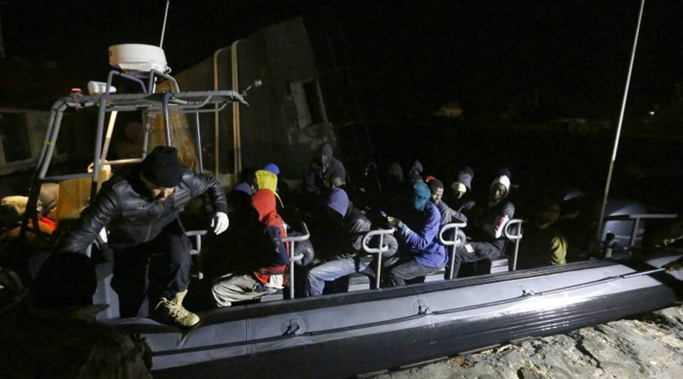 Libyan coast guard police help immigrants who were rescued at sea off the coast of Libya on Sunday.